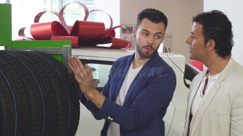 Ung representant som hjälper hans mogna kund som väljer bilgummihjul royaltyfri bild