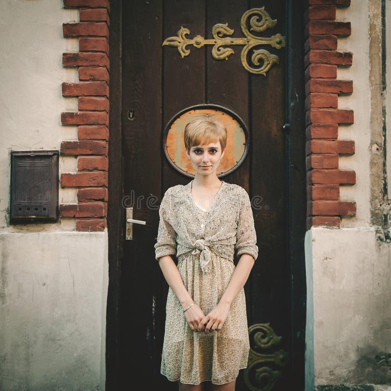 Ung resande flicka: stå nära en gammal dörr fotografering för bildbyråer