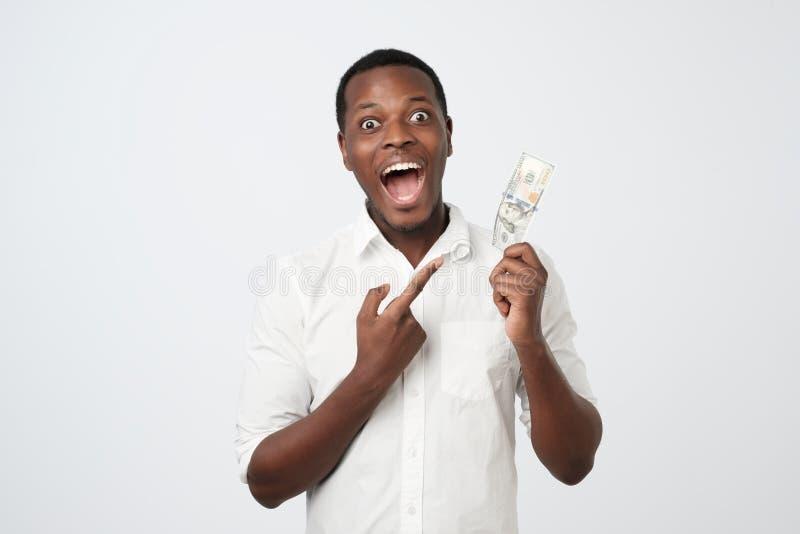 Ung rik afrikansk amerikanman i skjortainnehav hundra dollar med överraskning royaltyfria bilder