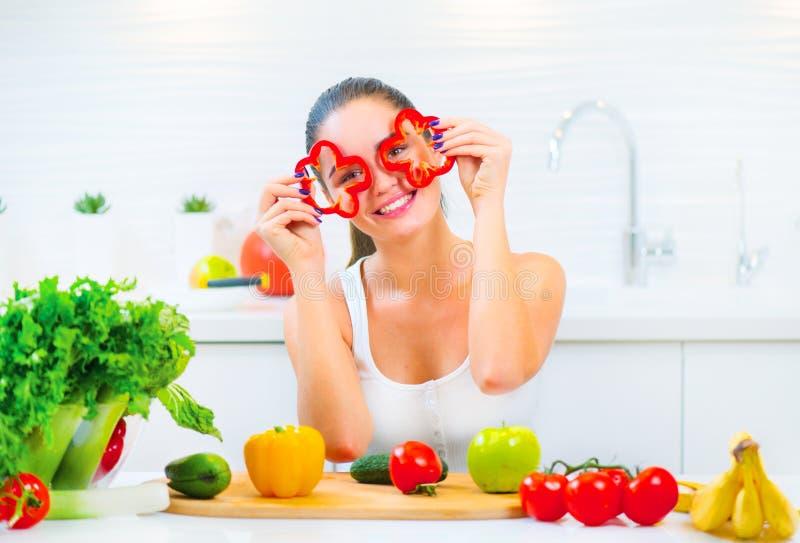 Ung rolig kvinna för skönhet som rymmer nya grönsaker i hennes kök hemmastadda arkivbild