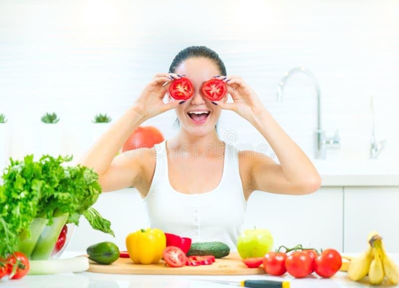 Ung rolig kvinna för skönhet som rymmer nya grönsaker i hennes kök hemmastadda royaltyfria bilder