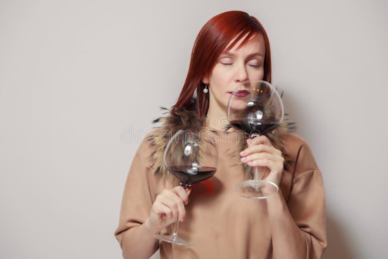 Ung rolig redhaired flickasommelier med pälsudde på den vita bakgrundshållen och lukten två exponeringsglas rött vin Begreppsalko arkivfoton