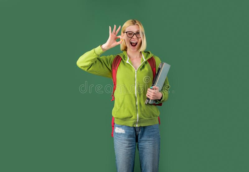 Ung rolig student i exponeringsglas och med boken ?ver gr?n svart tavlabakgrund Stående av den idérika unga le kvinnlign arkivbilder