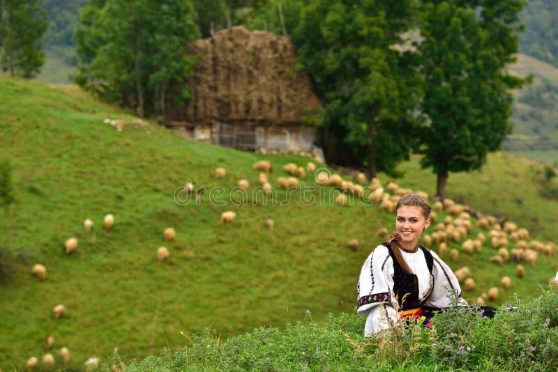 Ung rumänsk flicka som ler, gammalt herdehus i bakgrunden royaltyfria foton