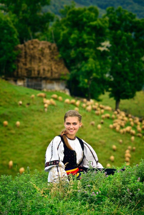 Ung rumänsk flicka som ler, gammalt herdehus i bakgrunden arkivbilder
