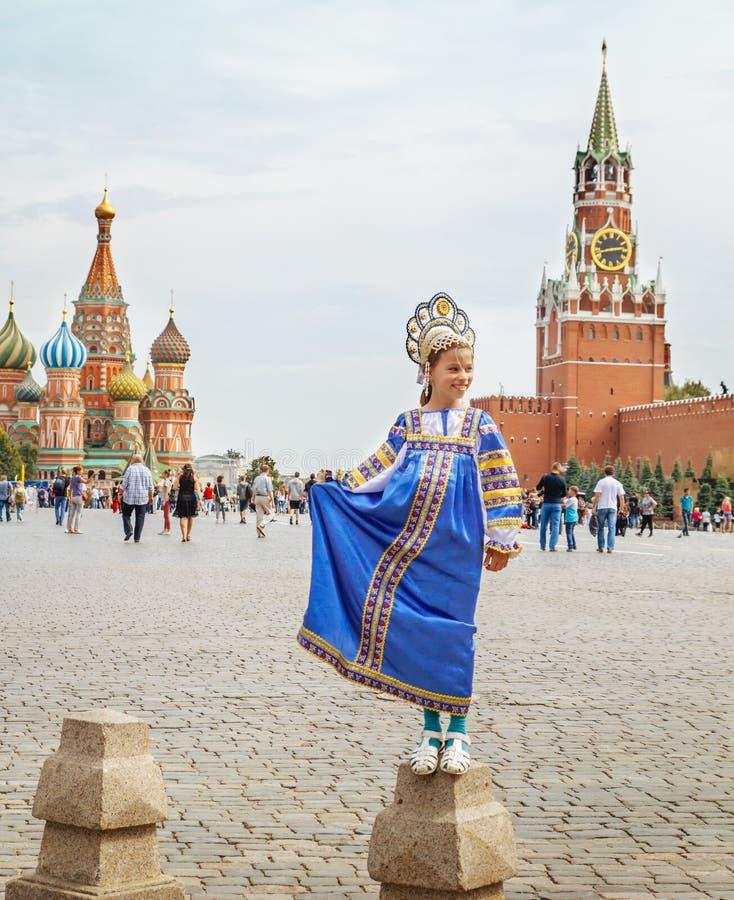 Ung ryssflicka som bär den traditionella dräkten på den röda fyrkanten i Moskva fotografering för bildbyråer
