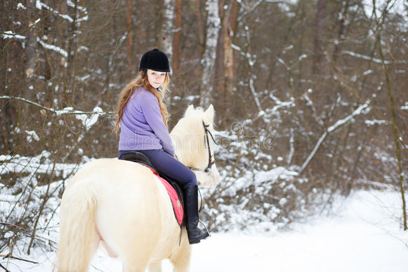 Ung ryttareflicka på albinohäst i vinterskog royaltyfri bild