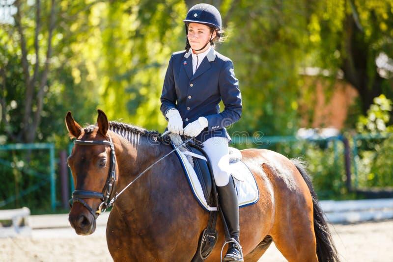 Ung ryttareflicka på häst på dressyrkonkurrens royaltyfria bilder