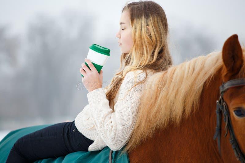 Ung ryttareflicka som kopplar av på hästrygg med kaffe royaltyfria bilder