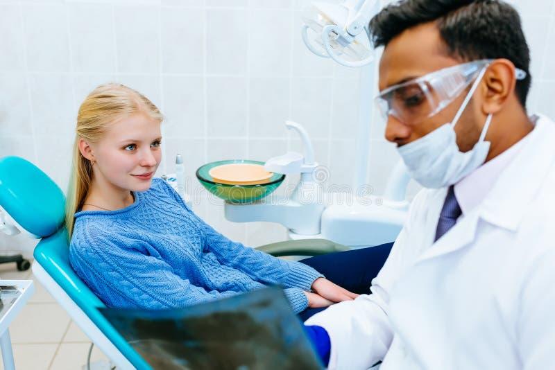 Ung säker asiatisk manlig tandläkare som kontrollerar strålen för tänder x av patienten Tand- klinikbegrepp fotografering för bildbyråer