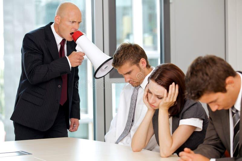 Ung säker caucasian affärsman som skriker på hans anställd royaltyfri foto