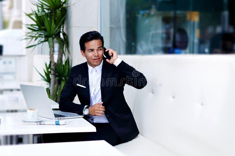 Ung säker man som talar på den smarta telefonen under arbetsavbrott i modern coffee shop royaltyfria foton