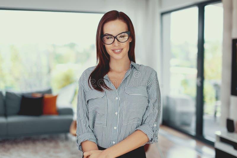 Ung säker modern nerdkvinna som poserar i vardagsrum arkivfoton