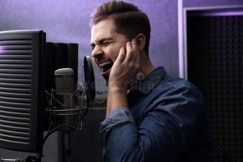 Ung sångare med mikrofoninspelningsång royaltyfria bilder
