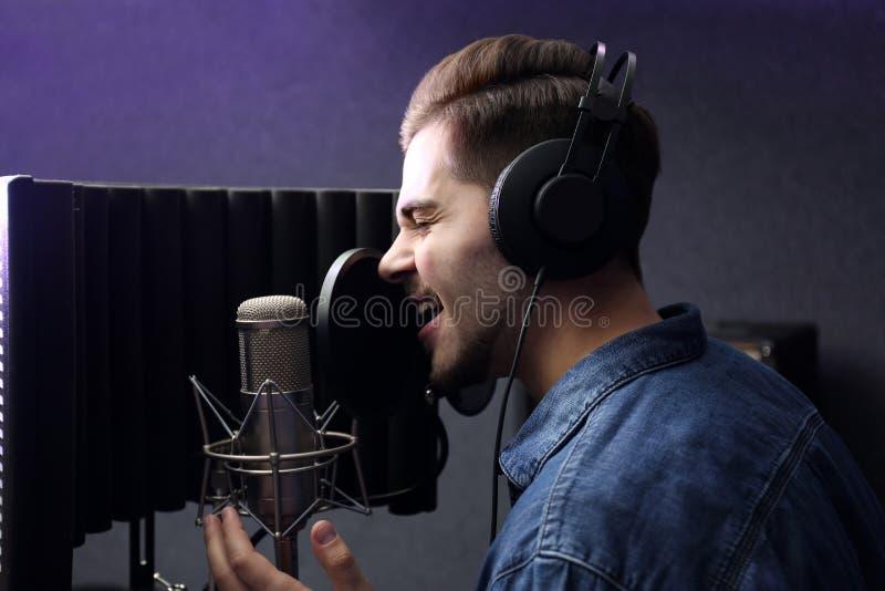 Ung sångare med mikrofoninspelningsång arkivbilder