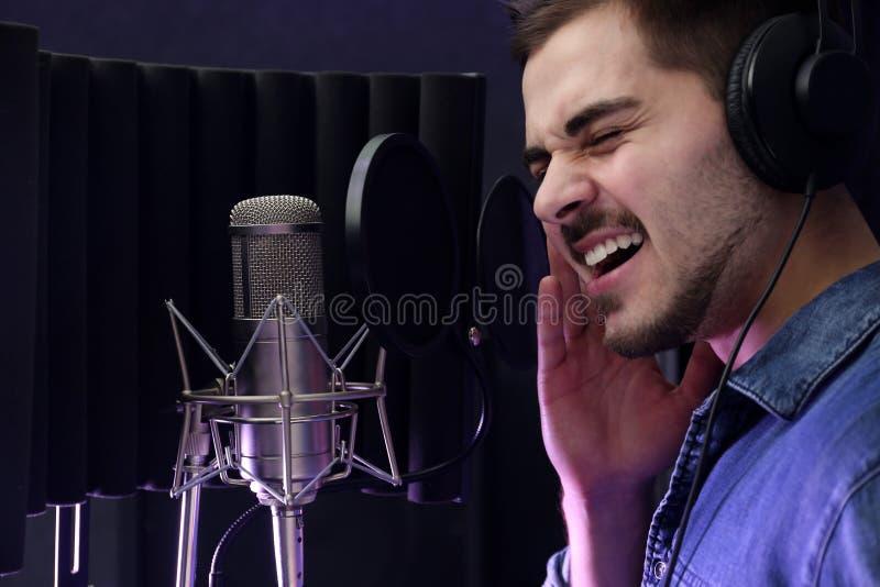 Ung sångare med mikrofoninspelningsång arkivbild