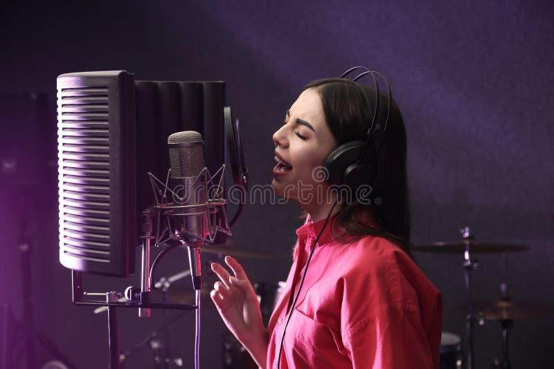 Ung sångare med mikrofoninspelningsång royaltyfria foton