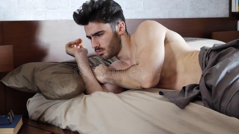 Ung sömnig man som ligger i säng som vaknar upp royaltyfria bilder