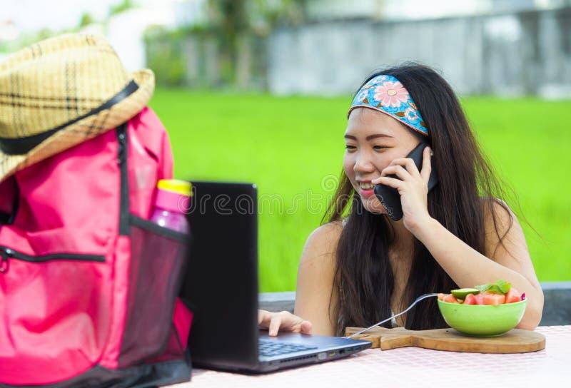 Ung sötsak och nätt asiatisk kinesisk fotvandrareflicka som direktanslutet arbetar med samtal för bärbar datordator som är lyckli royaltyfri foto
