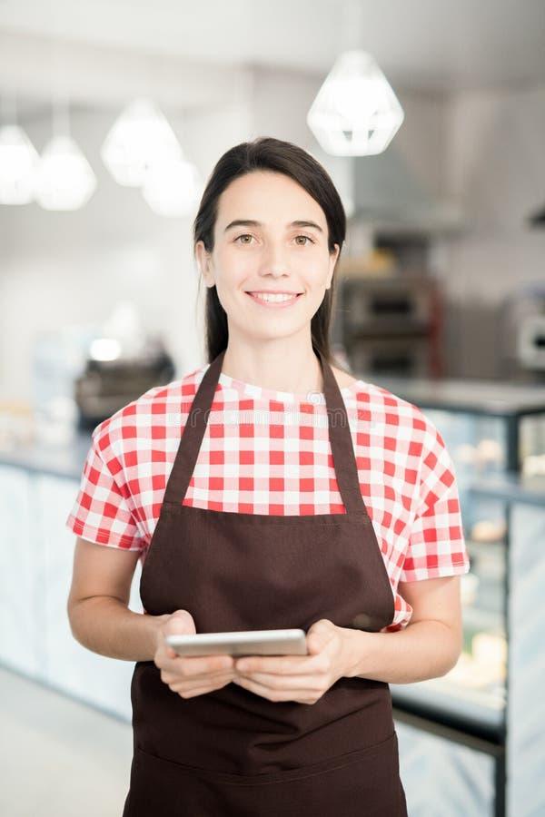 Ung servitris Posing i kafé royaltyfri bild
