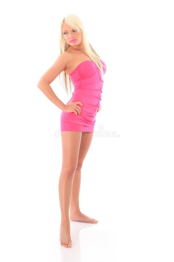 Ung sexig blond kvinna i en rosa klänning Isolerat på vit royaltyfria bilder
