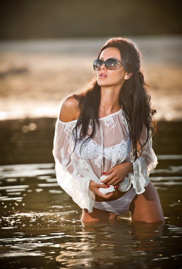 Ung sexig brunettflicka i den våta vita blusen som provocatively poserar i vatten Sinnlig attraktiv kvinna med svart solglasögon, arkivfoton