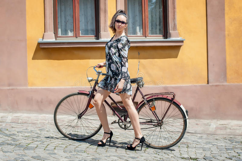Ung sexig brunettflicka med den gamla retro stiltappningcykeln arkivbilder