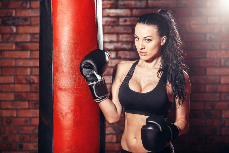 Ung sexig flicka med boxninghandskar som stansar påsen fotografering för bildbyråer