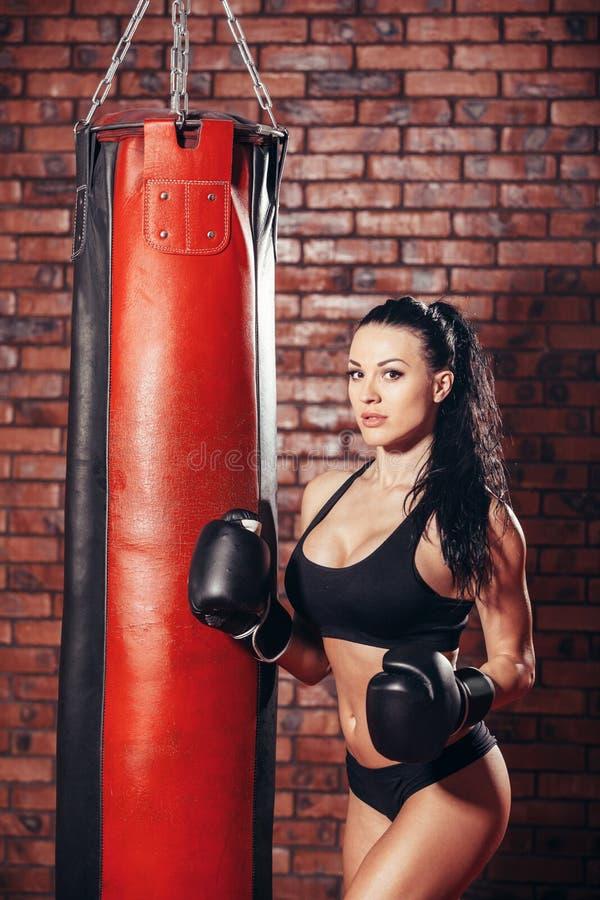 Ung sexig flicka med boxninghandskar som stansar påsen royaltyfri foto