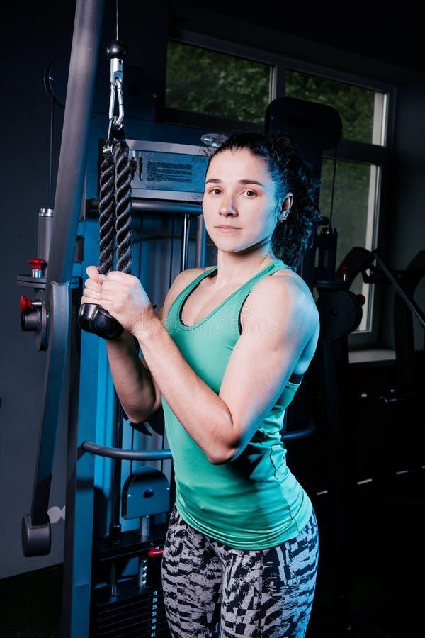 Ung sexig konditionkvinnagenomkörare med utbildningsmaskinen i idrottshallen arkivbilder
