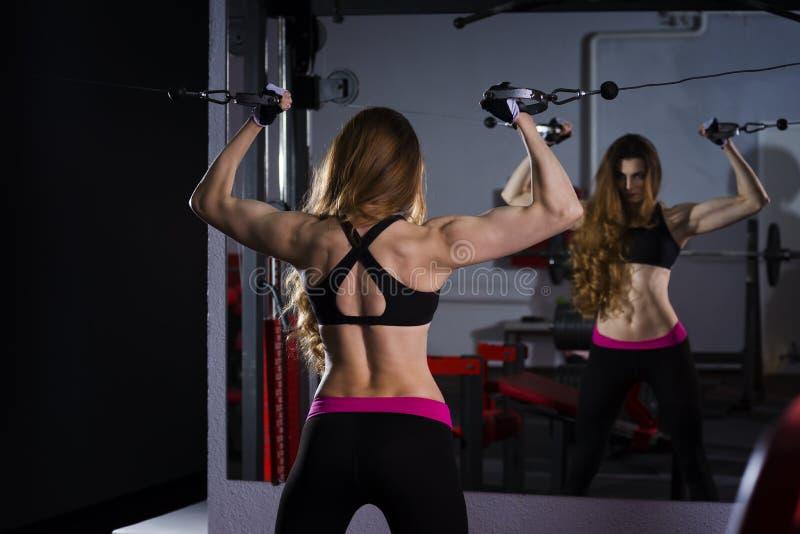 Ung sexig konditionkvinnagenomkörare med utbildningsmaskinen i idrottshallen royaltyfri fotografi