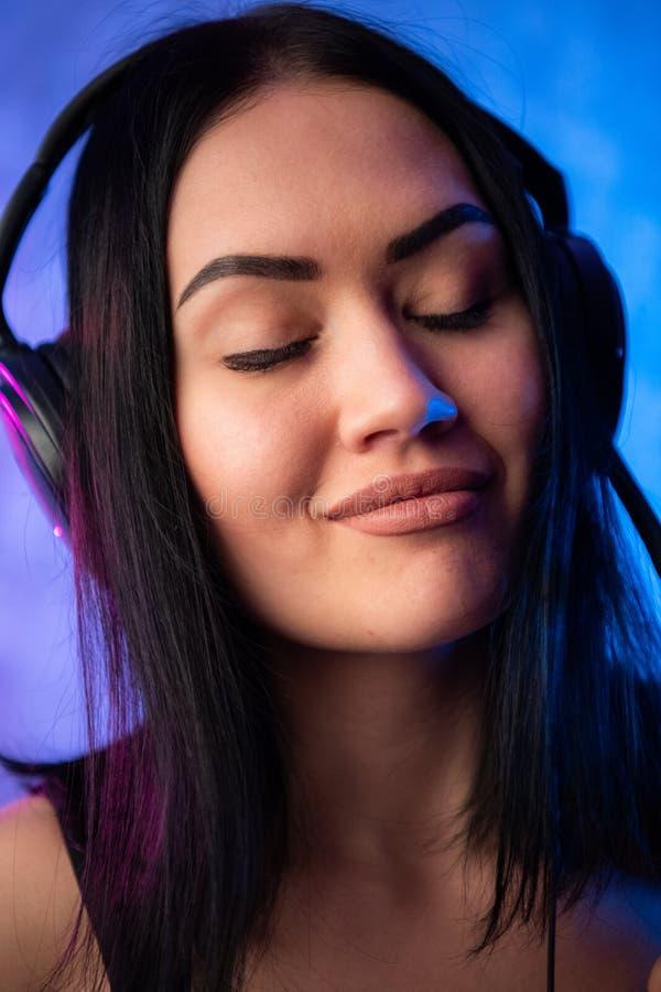 Ung sexig kvinna eller flicka dj med mörkt hår på nätt allvarlig sexig framsida i svart skjorta med musikalisk stereo- hörlurar e fotografering för bildbyråer