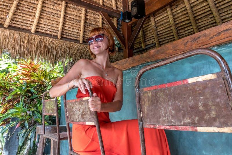 Ung sexig kvinna i röd klänning i ett tropiskt kafé på bakgrunden av palmträd och tropiska växter bali indonesia royaltyfri fotografi