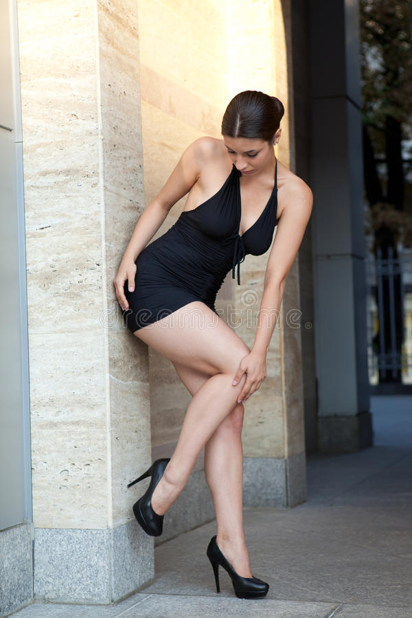 Ung sexig kvinna med den svarta klänningen arkivbild