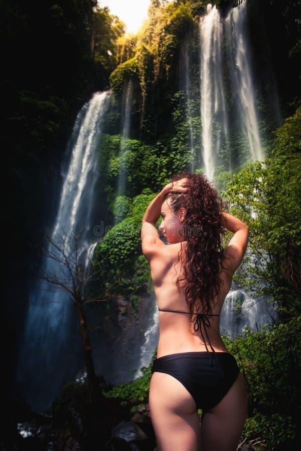 Ung sexig kvinna som ser vattenfallet i djungler Ecotourism royaltyfri fotografi