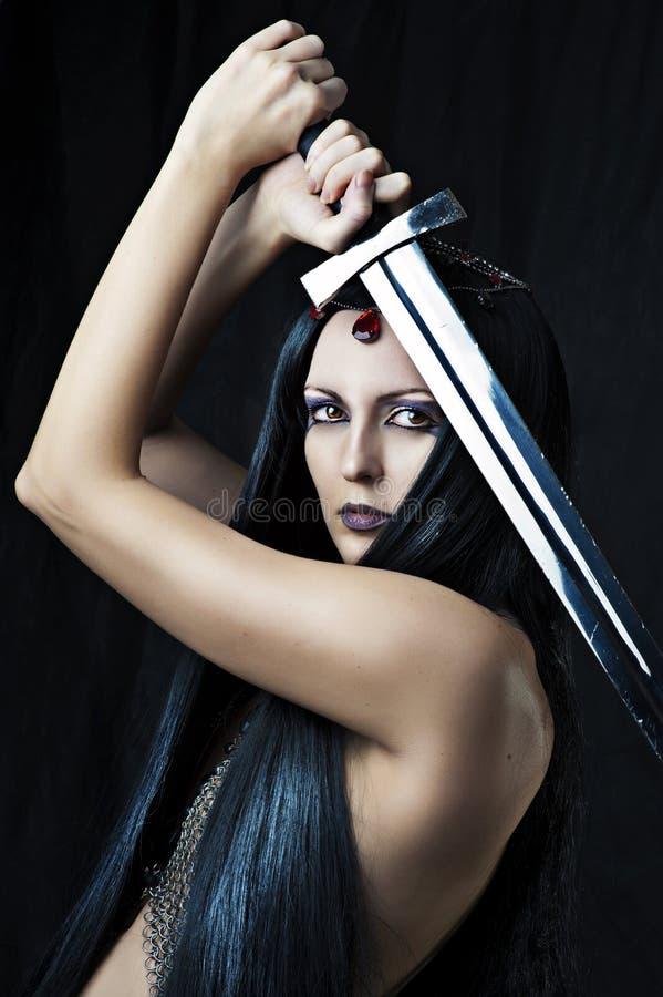Ung sexig kvinnakrigare med svärd royaltyfria bilder