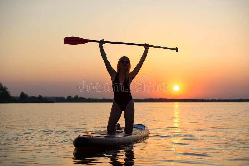 Ung sexig kvinnasimning står på upp skovelbrädet Vattensportar, aktiv livsstil royaltyfria bilder