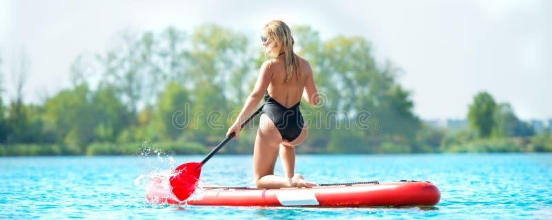 Ung sexig kvinnasimning står på upp skovelbrädet Vattensportar, aktiv livsstil royaltyfri foto