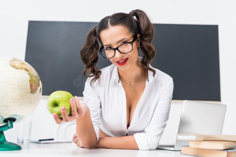 ung sexig lärare med grönt äpplesammanträde på arbetsplatsen royaltyfri fotografi