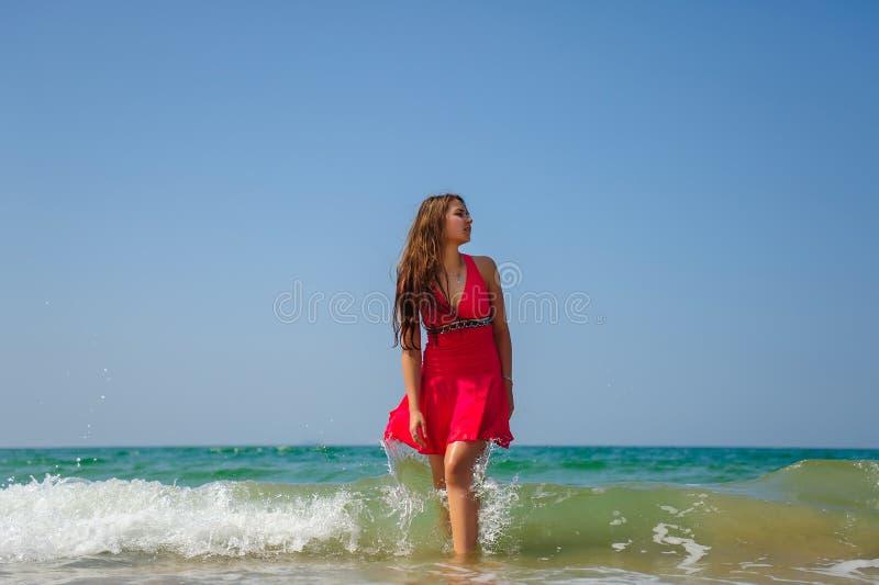 Ung sexig lång haired brunett i rött klänninganseende i vågor med vitt skum på havsbakgrund och blå himmel på varm dag royaltyfria bilder