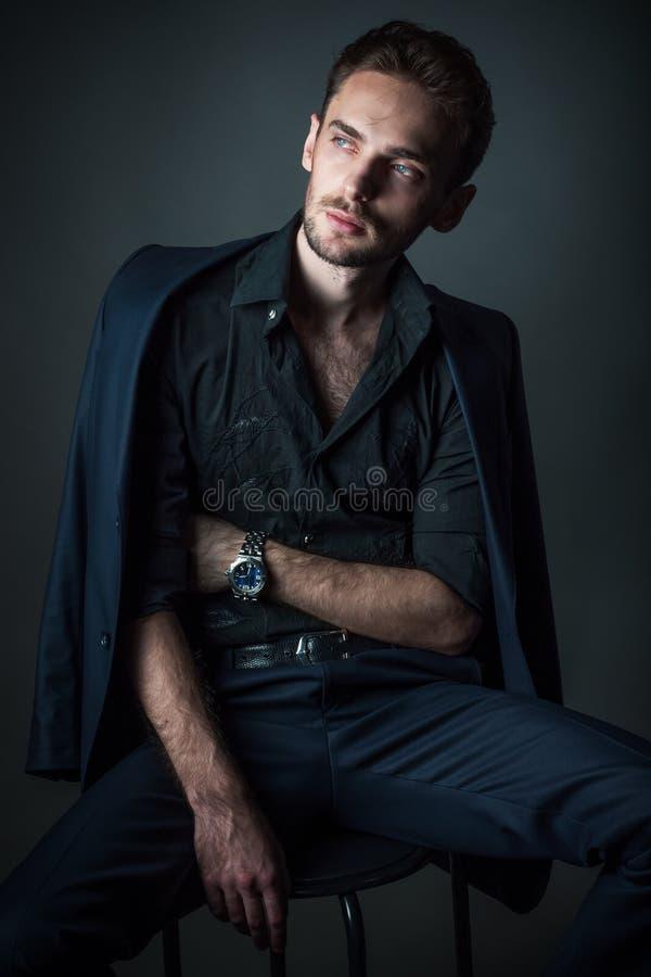 Ung sexig man i ett klassiskt dräktsammanträde på en stol royaltyfria foton