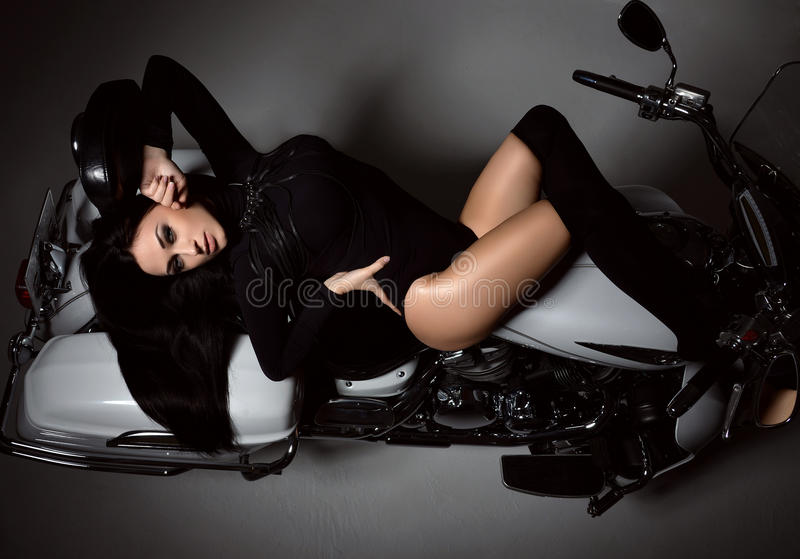Ung sexig modekvinna som ligger på motorcykelcykeln royaltyfri fotografi