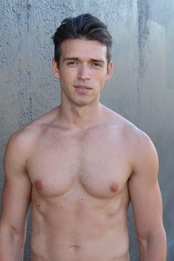 Ung sexig muskulös macho man som poserar med den nakna torson på grå bakgrund royaltyfri bild