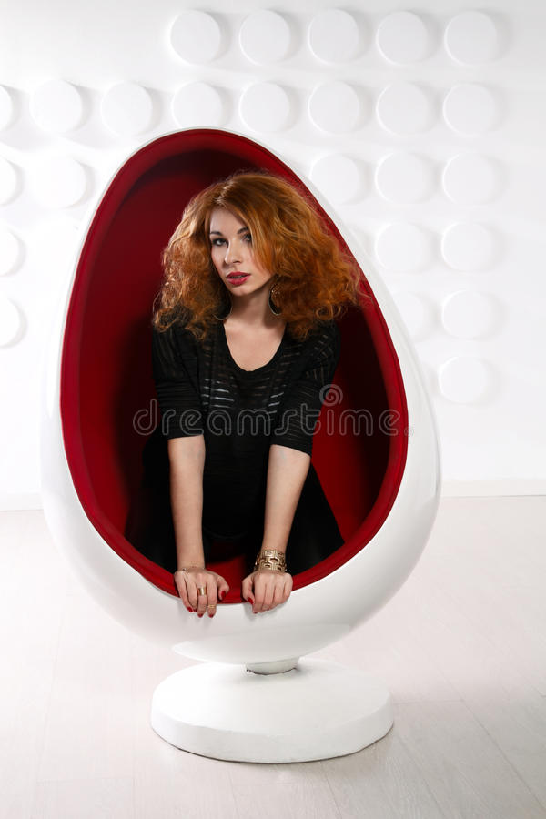 Ung sexig rödhårig mankvinna i ägg-stol arkivbilder