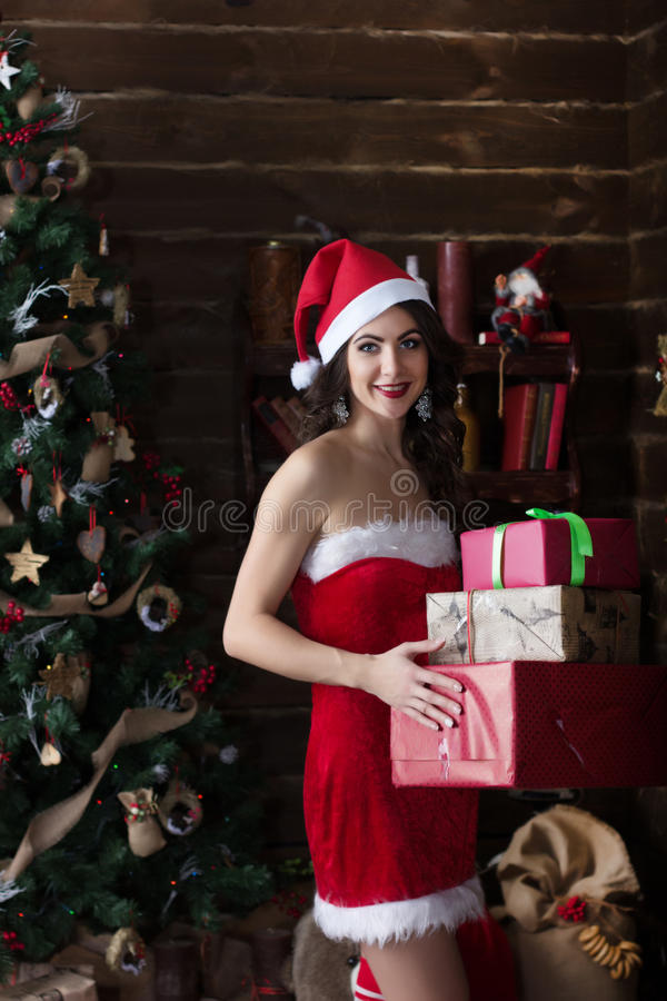 Ung sexig snöjungfru i röd klänningställning på trädet för nytt år med julklapp royaltyfri bild