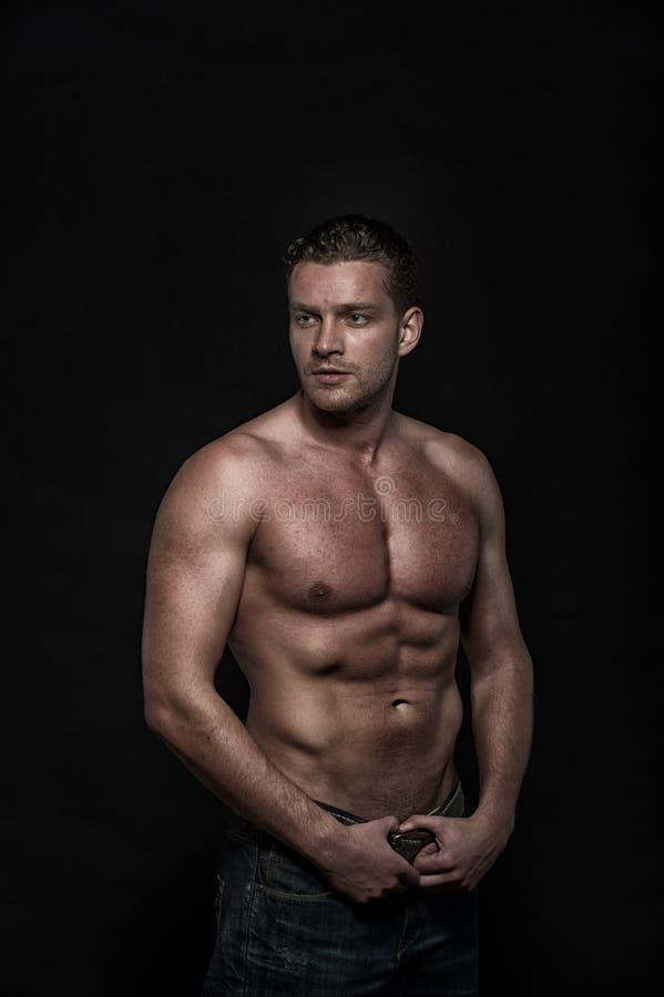 Ung sexig stilig idrotts- man med den nakna torson på mörk bakgrund royaltyfria foton