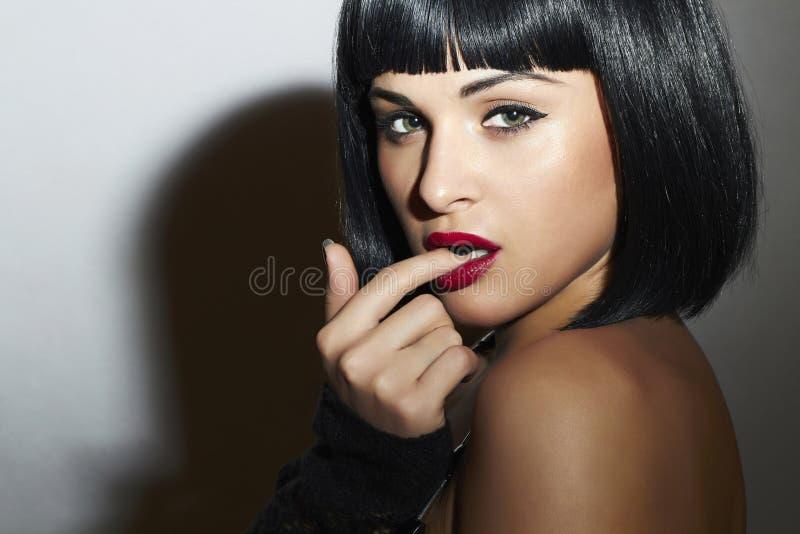 Ung sexig Woman.bob frisyr för Eautiful brunett. röda kanter arkivfoton