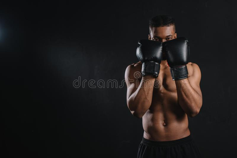 ung shirtless afrikansk amerikanboxare i boxninghandskar som ser kameran royaltyfri foto