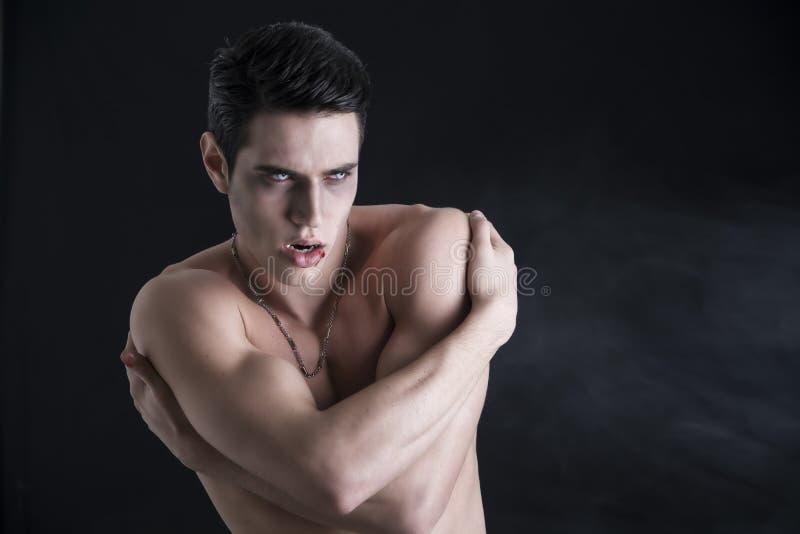 Ung Shirtless vampyrman och att göra en gest till kameran arkivfoton