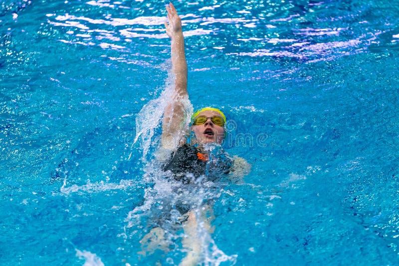 Ung simningryggsim för kvinnlig idrottsman nen sprintar in avstånd i pöl royaltyfria foton